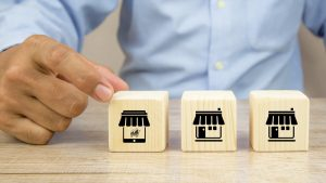 Close-up Hand Choosing Cube Wooden Blocks Stack With Franchise Business Store